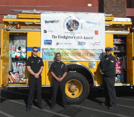 "Firefighters of Southern Nevada Burn Foundation fill the fire truck with toys for Las Vegas children during the 10th Annual ""Fill the Fire Truck Toy Drive."" Pictured left to right: Ryan Tidwell – Firefighter, Clark County Fire Department; Ronald Lourenco – Firefighter, Clark County Fire Department; Matt Peltier – Captain, North Las Vegas Fire Department."