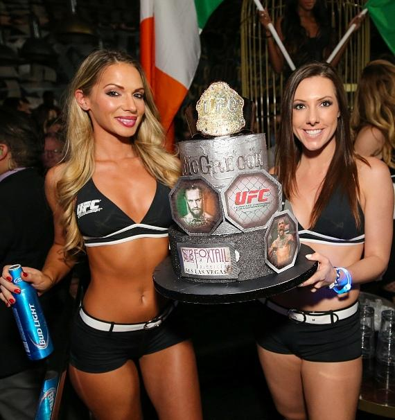 UFC girls present a celebratory cake to Conor McGregor following his win against Jose Aldo