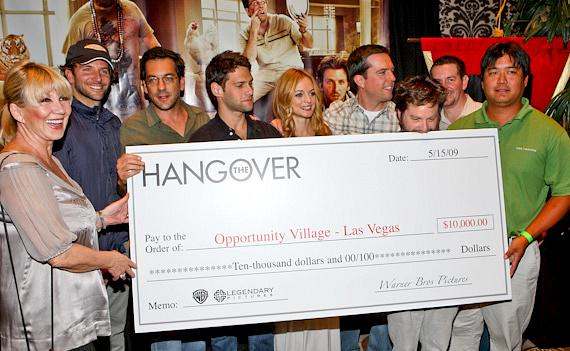 Linda Smith (left) accepts the check on behalf of Opportunity Village and Aaron Wong (far right) who came in 1st place