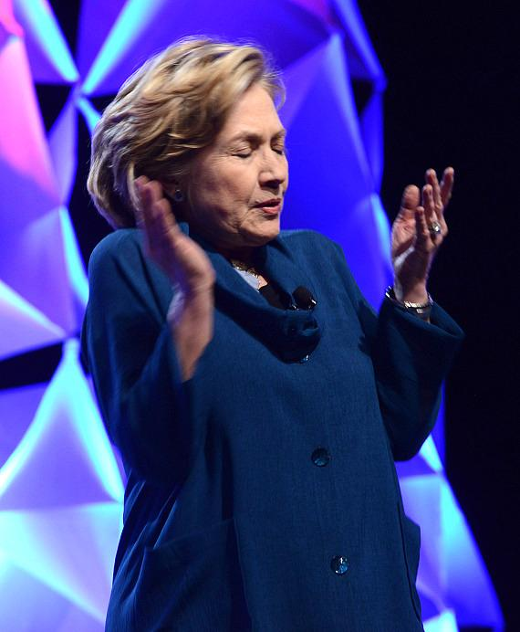 Former U.S. Secretary of State Hillary Rodham Clinton dodges a shoe thrown by a woman in the audience