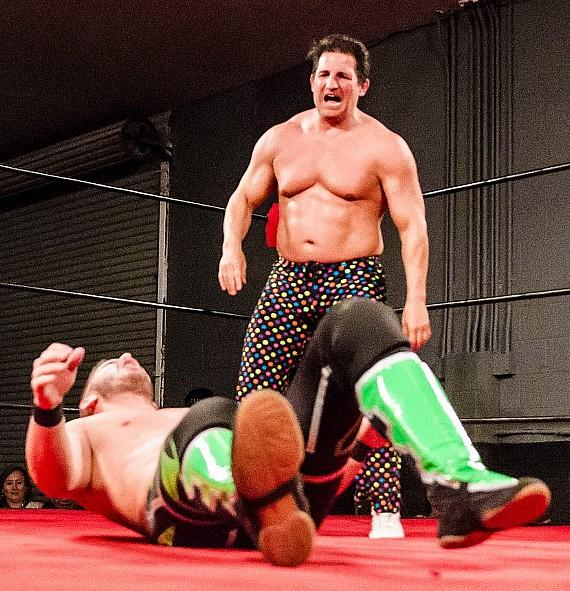 Disco Inferno standing over Evan Daniels