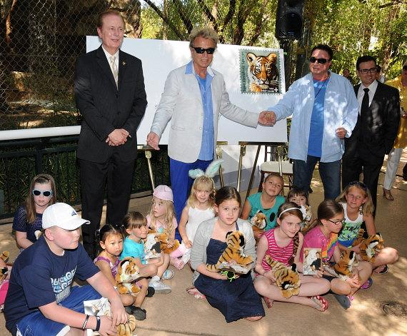 Craig Colton, Postmaster of Las Vegas, Siegfried & Roy and Franz Kallao, vice president of hotel operations of The Mirage with children who are attending the event