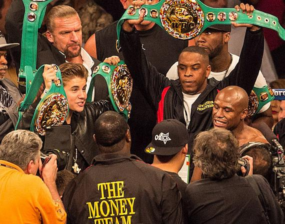 WWE's Triple H and Justin Bieber celebrate in the Ring with Floyd Mayweather