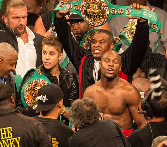WWE's Triple H (upper right corner) and Justin Bieber celebrate in the Ring with Floyd Mayweather