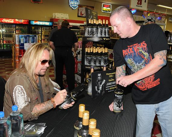 Vince Neil autographs a bottle of Tatuado vodka for customer at Lee's Discount Liquor