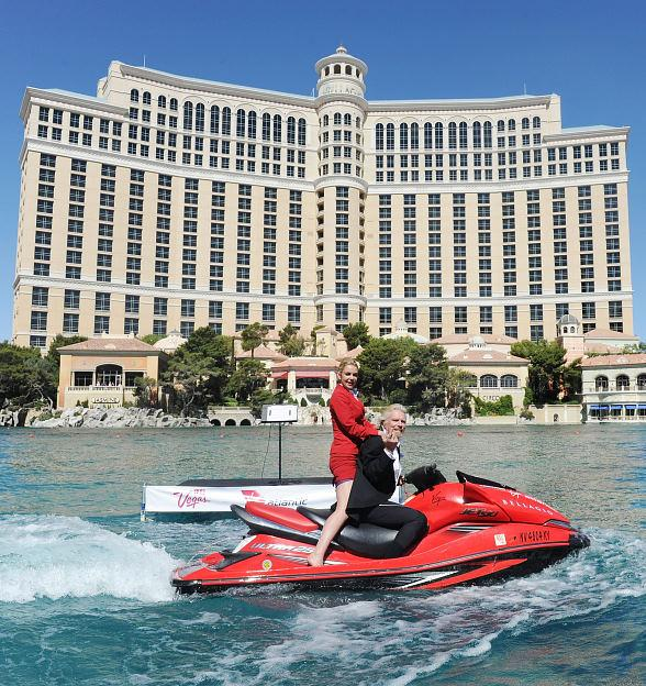 Sir Richard Branson and cabin attendant ride a jet ski in the Bellagio fountains pool