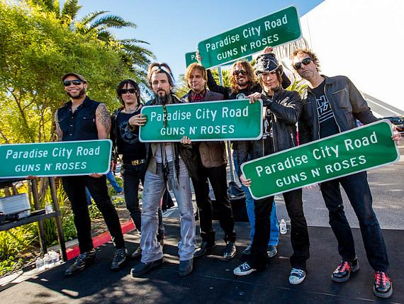 "Guns N' Roses band members pose with ""Paradise City Road"" sign at The Joint"