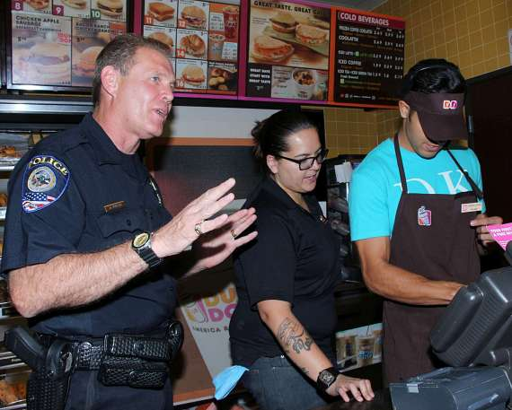 Officer from Clark County School District Police Department with BMX Pro Ricardo Laguna at Dunkin' Donuts benefit for Nevada Childhood Cancer Foundation