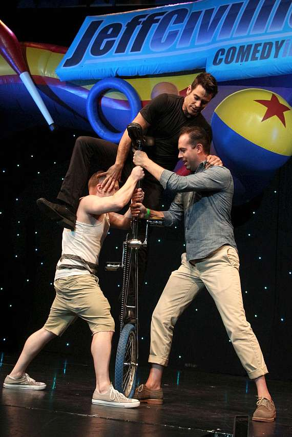 Volunteers help Jeff Civillico onto a large unicycle