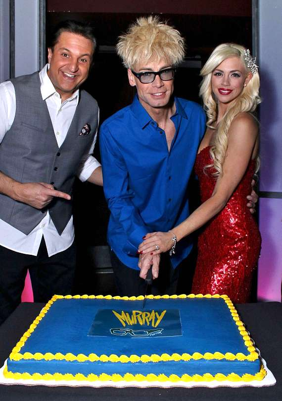 "Douglas ""Lefty"" Leferovich, Murray SawChuck and Chloe Crawford pose with a ""Murray"" cake"
