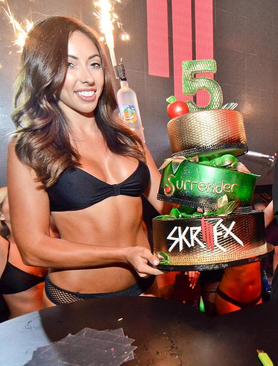Server with cake for Surrender Nightclub's 5-Year Anniversary Party