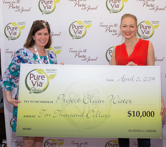 Pure Via Marketing Director Cheryl Gill and Jewel pictured as Jewel accepts 10K donation from Pure Via on behalf of Project Clean Water