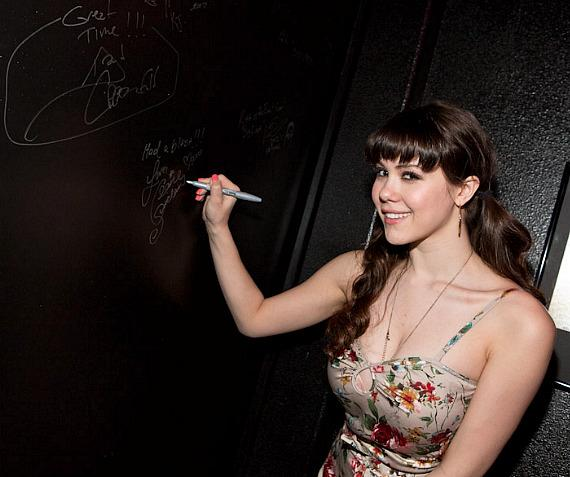 Claire Sinclair signs the elder door at KISS Monster Mini Golf in Las Vegas