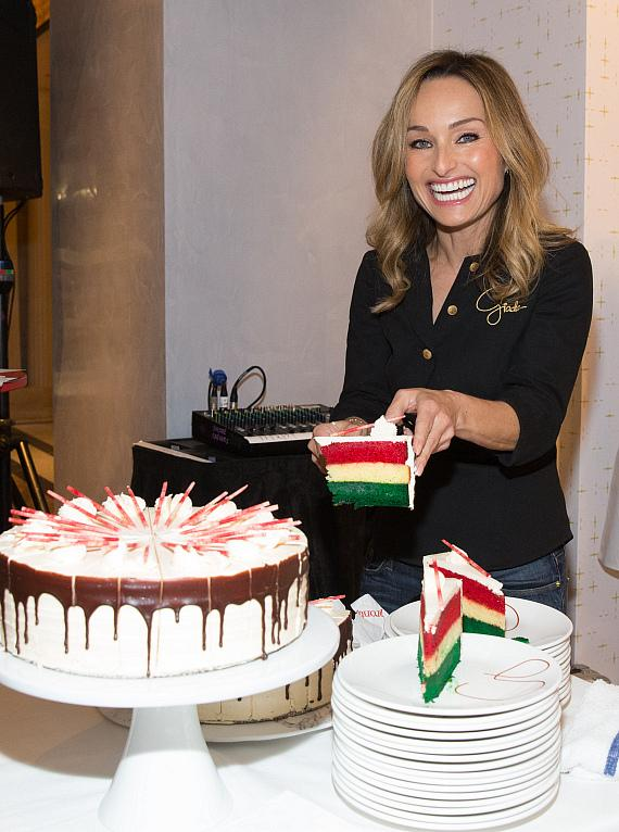 Giada De Laurentiis cuts slices of her Italian Rainbow almond cake to serve to guests.