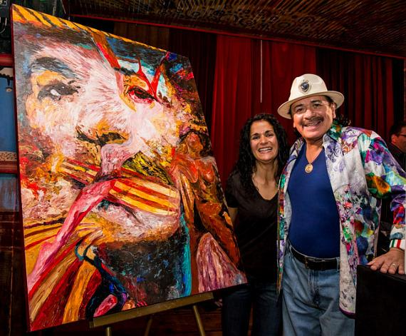 Carlos Santana with Stacy Economon who painted the portrait next to them