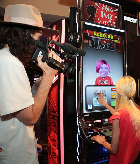 Tara Reid demonstrates how the new TMZ slot machine can capture her image and use it in game play