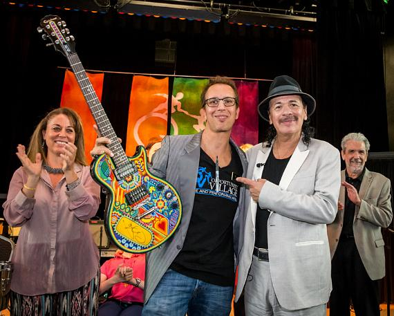 Carlos Santana meets Opportunity Village's band The OVertones after they performed a Santana music medley during his visit to the organization's Ralph and Betty Engelstad Campus on Tuesday, September 15, 2015, where he and longtime associate Hermes Music donated more than 60 instruments.