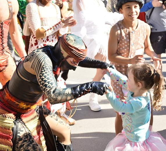 A performer from KA plays with a child