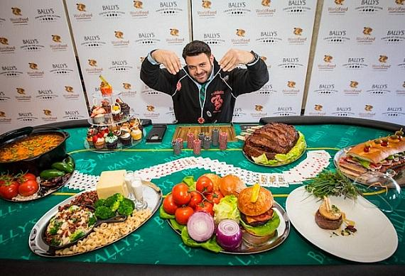 Adam Richman at the Bally's Las Vegas press conference behind a poker table filled with items representing each of the seven food-category competitions at the WFC
