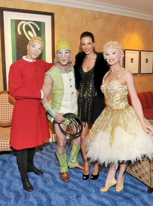 "Alessandra Ambrosio poses before the show with characters from ""O"" by Cirque du Soleil"