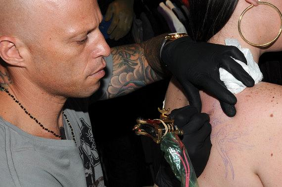 Ami James draws the outline of the tattoo