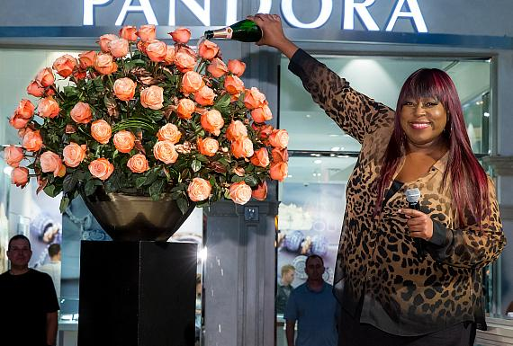 As is tradition in the floral industry, Loni Love douses the new bud with champagne
