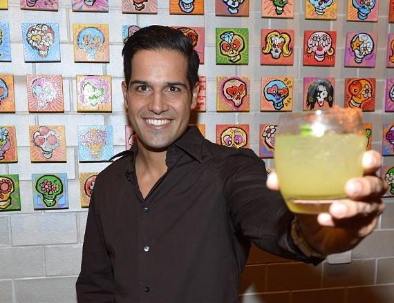 Ricardo Laguna enjoys a cocktail in front of artwork done by graffiti artist Erni Vales
