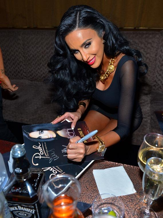 Lilly Ghalichi autographs her poster at Posh Boutique Nightclub