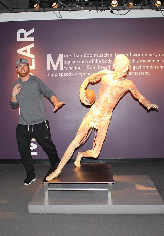 "Bruce Miller poses with ""Football Specimen"" at BODIES…The Exhibition"