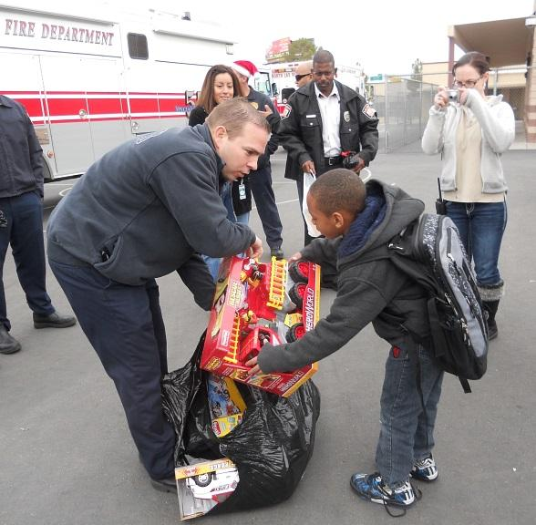 "Firefighter Ben Bodine hands out a toy fire truck to Kyirean Reed during a visit to Marion Cahlan Edison Elementary School where firefighters delivered toys to the students as part of Firefighters of Southern Nevada's 10th Annual ""Fill the Fire Truck Toy Drive."""