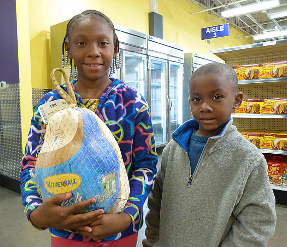 Kids with turkey at Catholic Charities Food Pantry