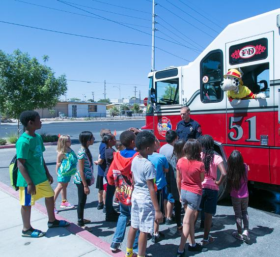 Children of the James Clubhouse of Boys & Girls Clubs of las vegas listen to fire safety tips from the North Las Vegas Fire Deparment and Sparky The Fire Dog