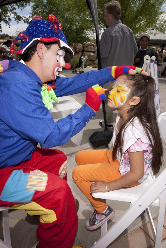 Clown painting a child's face at Día del Niño