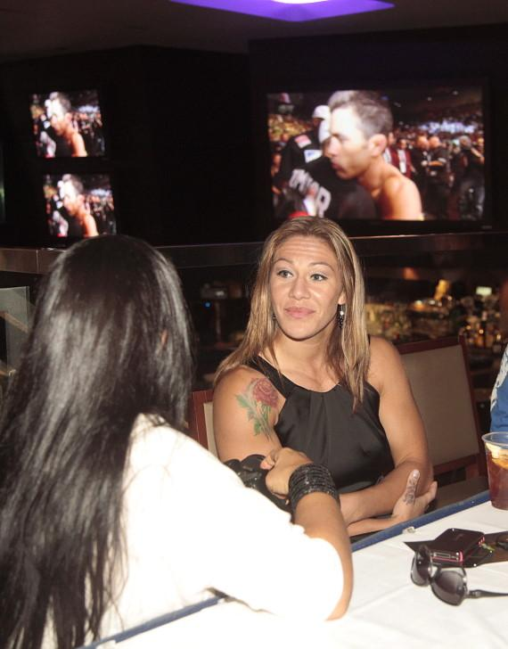 Couture and Cyborg signing autographs