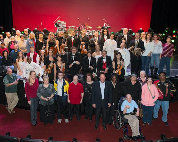 Performers and musicians from Mannheim Steamroller Christmas Las Vegas by Chip Davis pose on stage with staff, families and clients of Easter Seals Nevada after November 26, 2012 performance