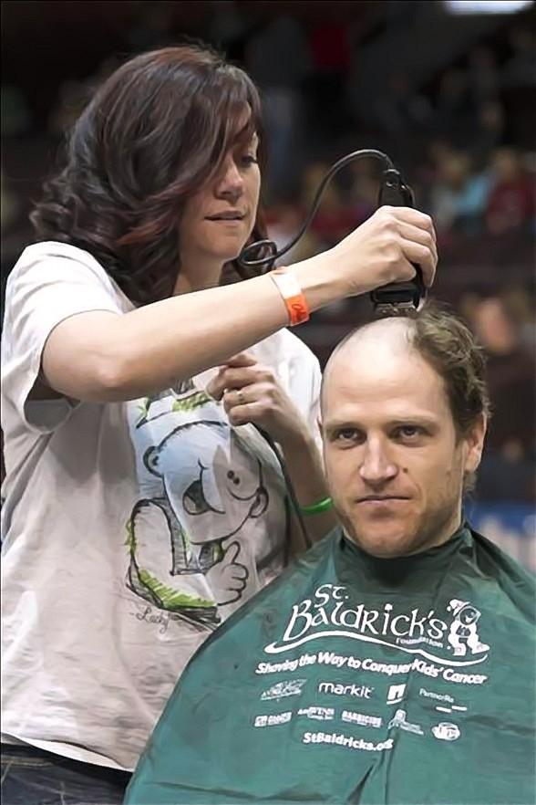 Wranglers center Ash Goldie gets his head shaved on the ice after raising $1,330 for St. Baldrick's