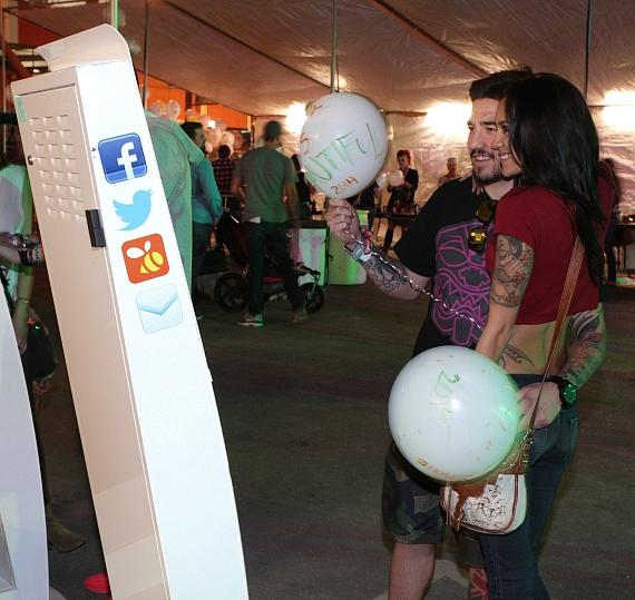 Guests pose for picture wall after decorating balloons at INSPIRED by the D at Life Is Beautiful festival, Las Vegas