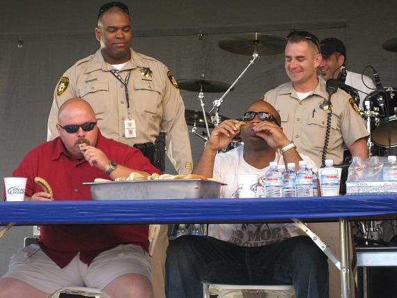 """Officers Jason Jennings and Victor Gray compete in the El Cortez """"Battle of the Bratwurst"""" eating contest while (back row from left) Officers Ramon Denby and Garret Vandereecken cheer them on."""