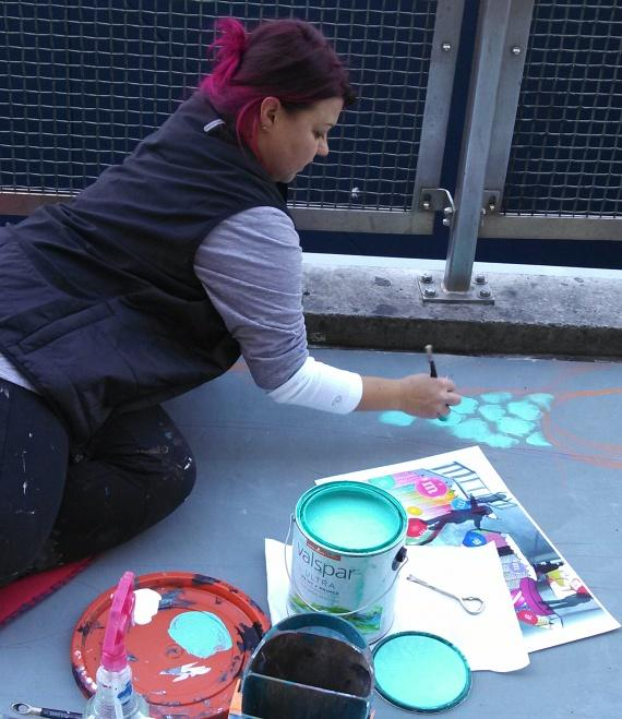 Artist from We Talk Chalk paints 3D drawing on the sidewalk outside the M&M store