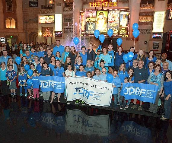 JDRF youth ambassadors and family members gathered in front of Miracle Mile Shops' blue fountain