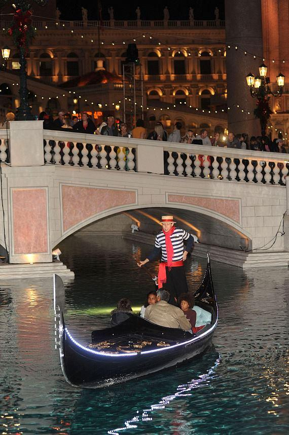 Gondolier appears under the Doge's Bridge as guests look on