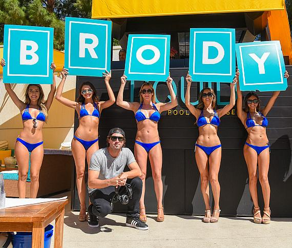 Bikini-clad cocktail waitresses signs proclaiming his name