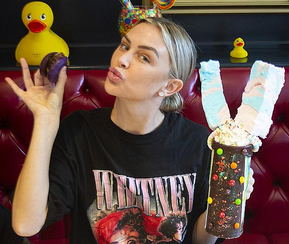 Lala Kent poses with purple rainbow slider and Tie Dye Insane Milkshake