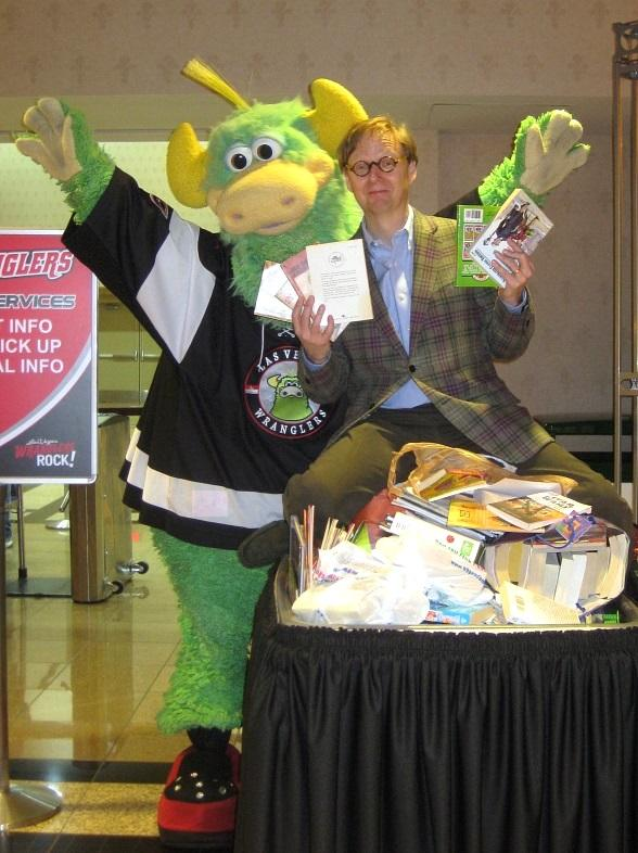 Mac King and Las Vegas Wranglers' mascot The Duke celebrate the more than 500 books donated at the hockey games on February 4 and 5