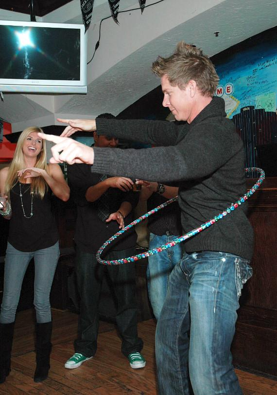 Mark Long playing hula-hoop with Trishelle Cannatella encouraging him with  laughter at McFadden's Restaurant