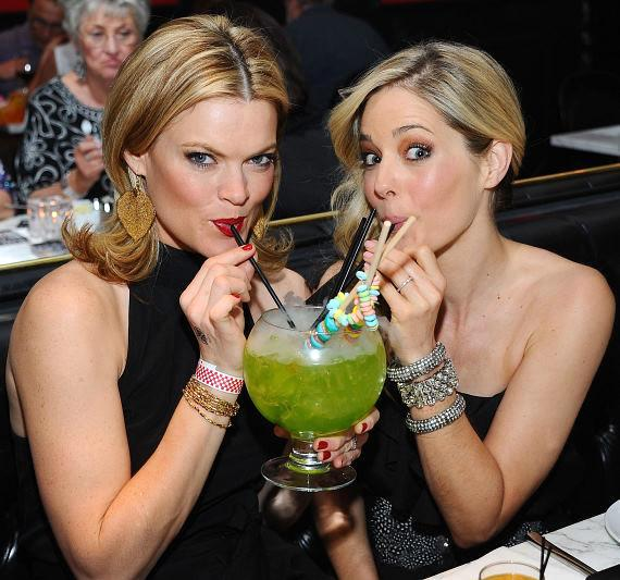 Missi Pyle (L) and Christina Moore (R) sip on a Lollipop Passion cocktail at Sugar Factory American Brasserie at Paris Las Vegas