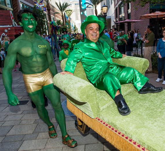"""Brian """"Lucky"""" Thomas is carried through The LINQ by muscular green men as the group kicks off O'Sheas St. Patty's Day Block Party"""