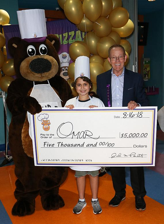 Omar accepting one of his prizes, a $5,000 check from IncrediBear and owner of John's Incredible Pizza Company, John Parlet