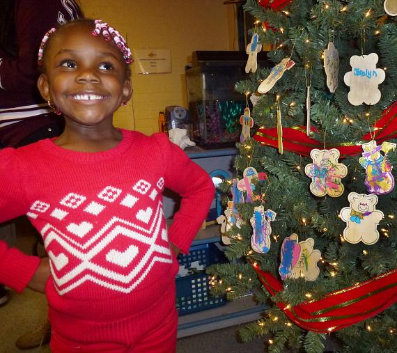 A child proudly shows off hand-made ornaments on a Christmas tree during the BOBS from Skechers event at Variety Early Learning Center in Las Vegas