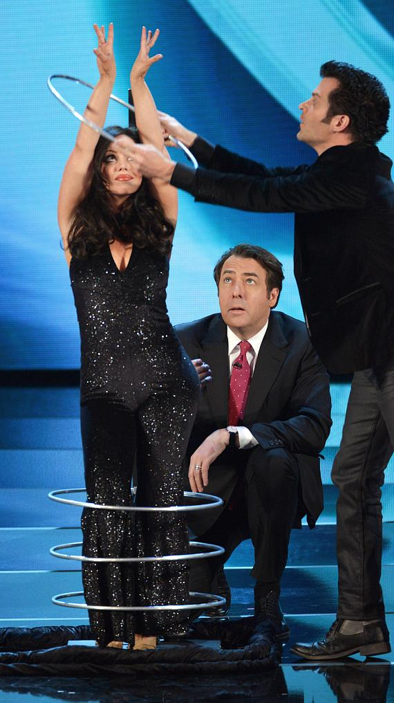 """Las Vegas Magicians Kyle Knight and Mistie perform on """"Penn and Teller: Fool Us"""" while host Jonathan Ross examines the metal rings"""